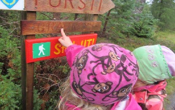 Barn som peikar på turskilt i Aukraskogen