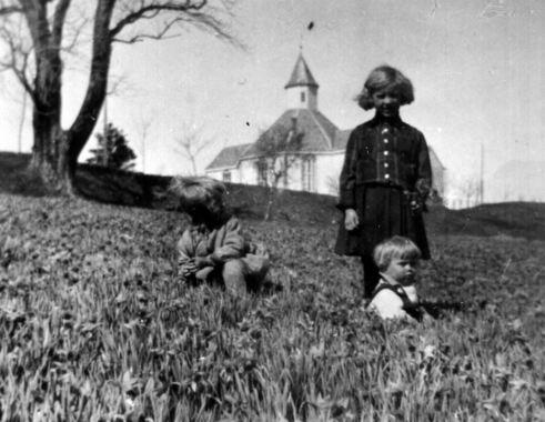 Tre prestebarn som pukkar blomar på påskeliljemarka. f.v. Maria Synøve, Synøve Maria og Steingrimm (sittande). Bilde tatt 1932. Givar: Mary Fanghol.