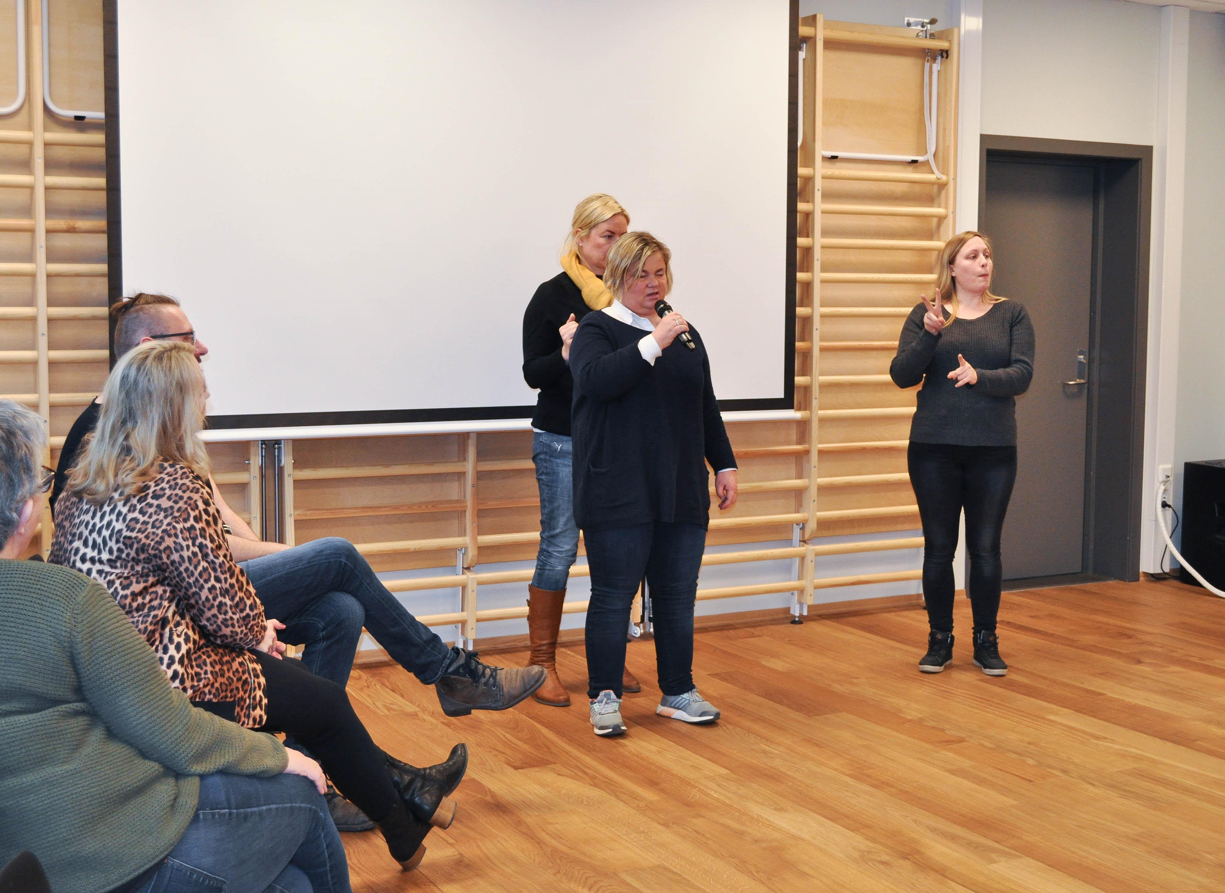 Bruker forteller om sine opplevelser. Hun får haptisk tolkning på ryggen og vanlig tolk til høyre. Tre lyttere til venstre.