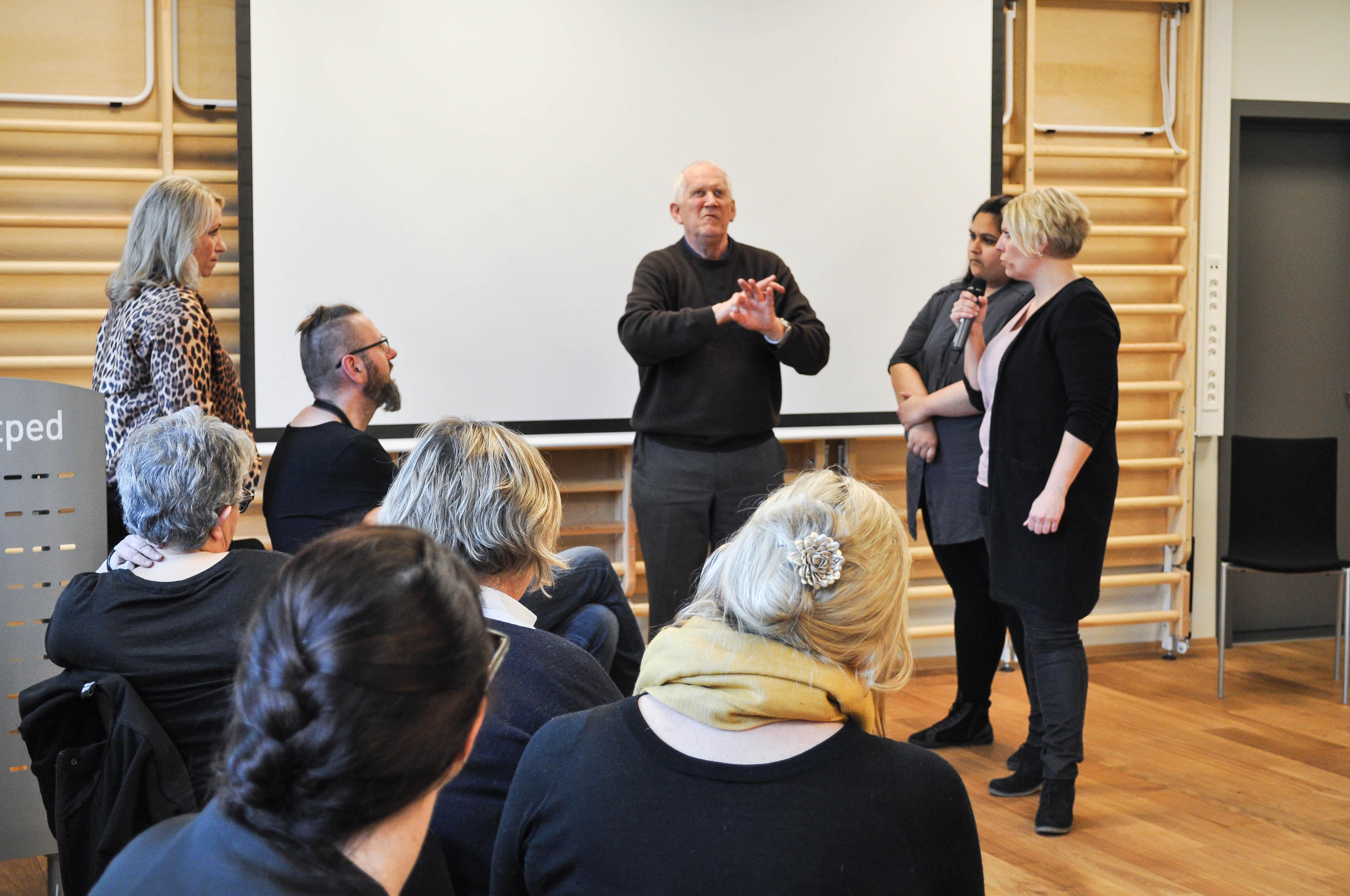 En eldre bruker forklarer på tegnspråk om sin overgang til å bli taktil tegnspråkbruker. Ved hans høyre side to tolker, til venstre seks lyttere.
