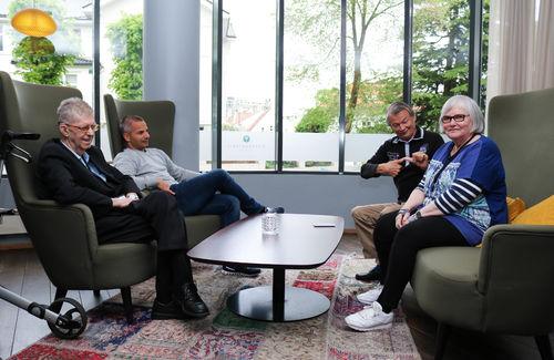 Tre FNDB-medlemmer (to menn og en kvinne), sitter sammen rundt et bord med en mannlig tolk-ledsager.