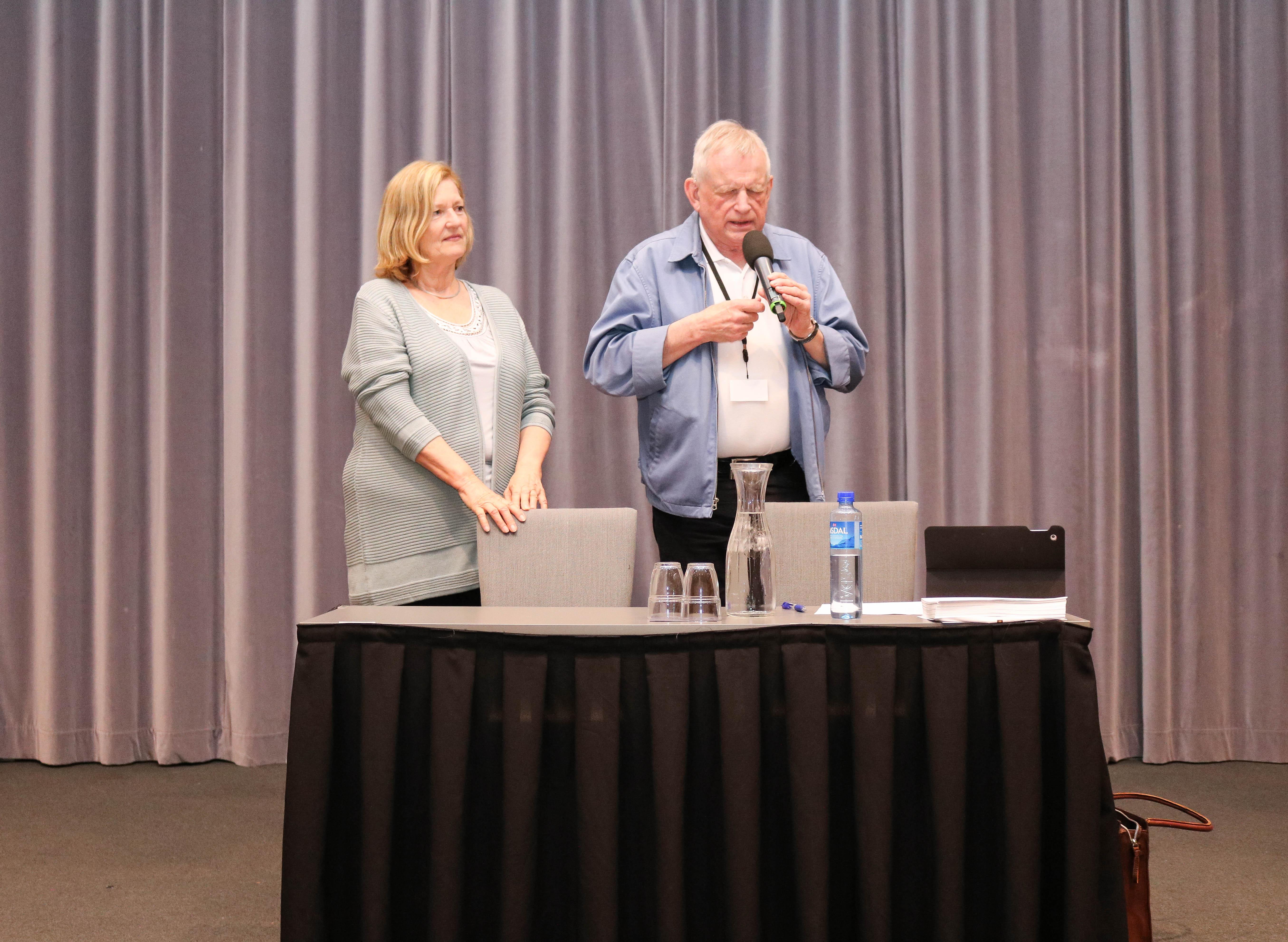 Leder for FNDB prater i mikrofon oppe på et podie, til venstre står en kvinnelig tolk-ledsager.