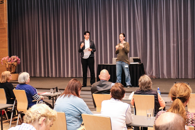 En kvinne fra NAV holder foredrag til FNDB, til høyre for henne står en kvinnelig tolk-ledsager.