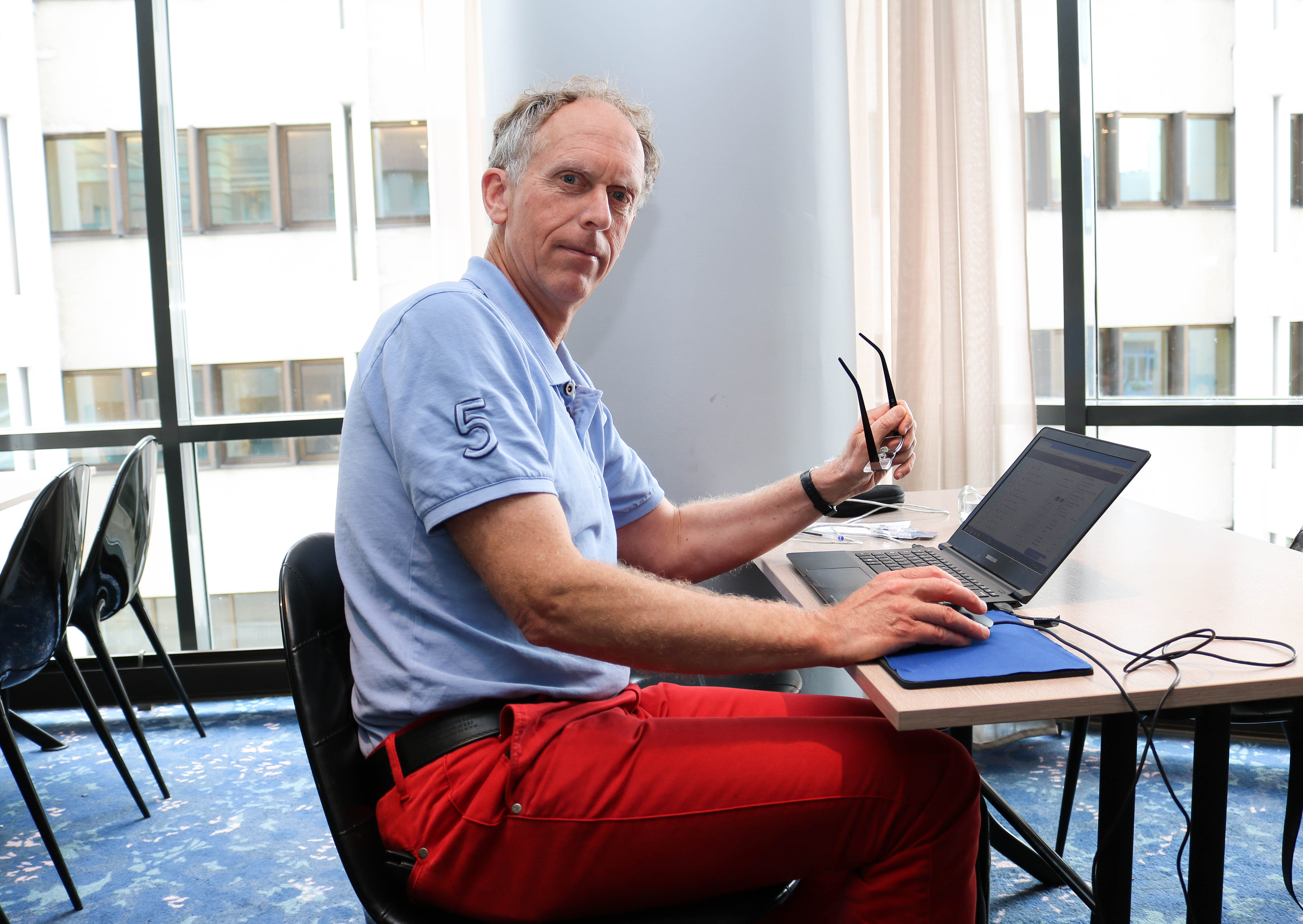 En mannlig FNDB-deltaker sitter med sin laptop i en pause.
