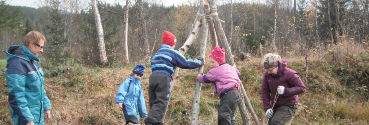 Bilde av barn og voksne som leker i skogen