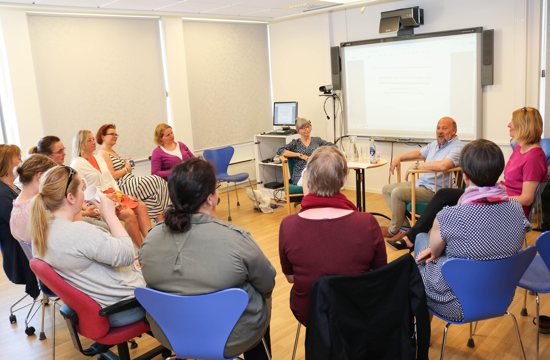 En gruppe med kvinner fra Regionsenteret for døvblinde i Tromsø sitter rundt Bertil Bjerkan i VK-rommet.