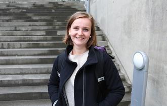 En smilende Ida skredlund med hendene i lomma foran betongtrappene ved Tromsø bibliotek og byarkiv.
