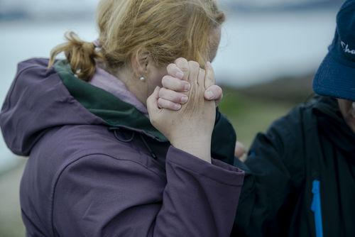 Kvinne kledd i lilla turjakke kommuniserer taktilt med å holde hånden til døvblind mann opp mot ansiktet sitt.