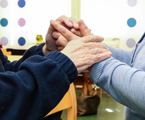 Nærbilde av to par med hender som møtes i taktil kommunikasjon.