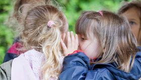 Barn hvisker og snakker sammen