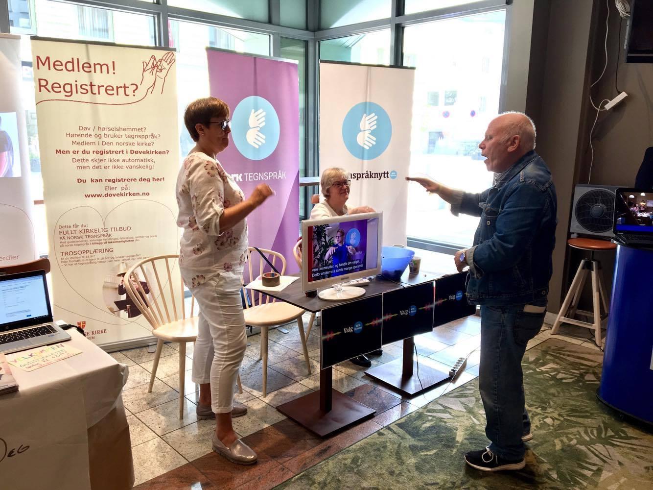 NRK-tegnspråk sin stand. En eldre mann diskuterer med to kvinner fra NRK-tegnspråk.