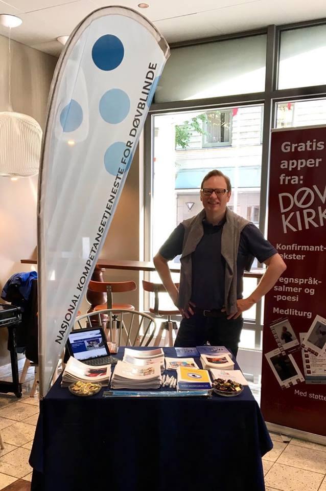 Roy-Morten Østerbøl, rådgiver innen prosjekt og web, poserer smilende foran NKDB-stand.