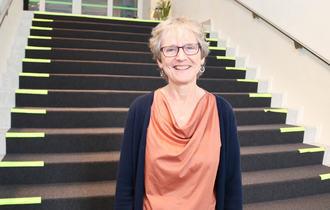 Portrettfoto av Marianne Disch foran en bred trapp på Ålborg kurs- og konferansesenter.