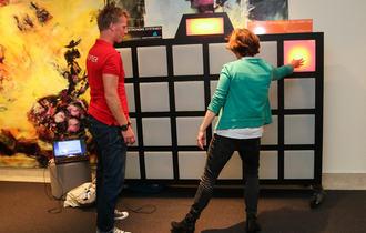 Kvinne med grønn genser tester en lystavle, mens mannlig frivillig med rød t-skjorte viser henne teknikken.