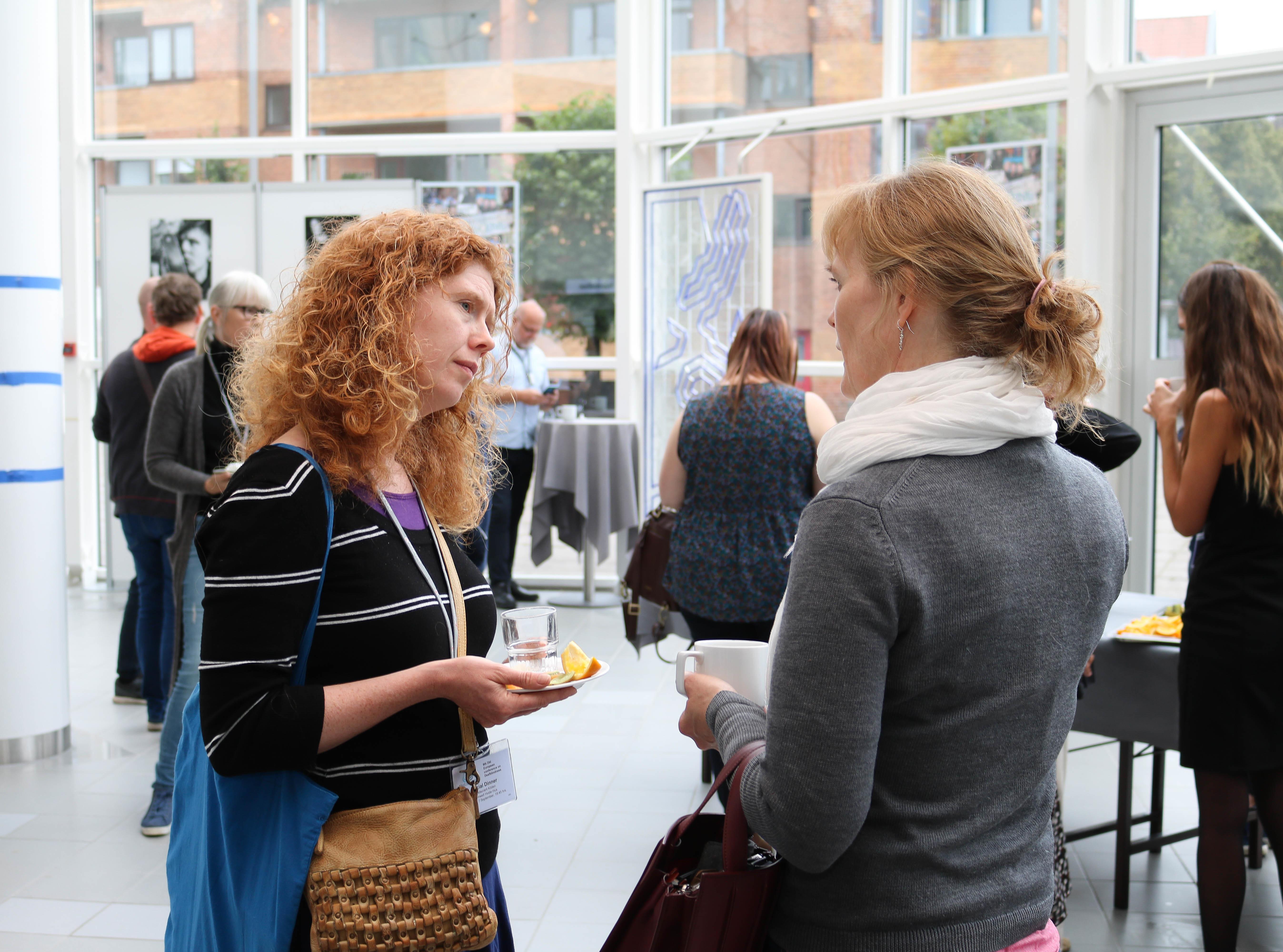 To kvinner diskuterer med hverandre under en av pausene i konferansen. Flere andre personer står i bakgrunnen.