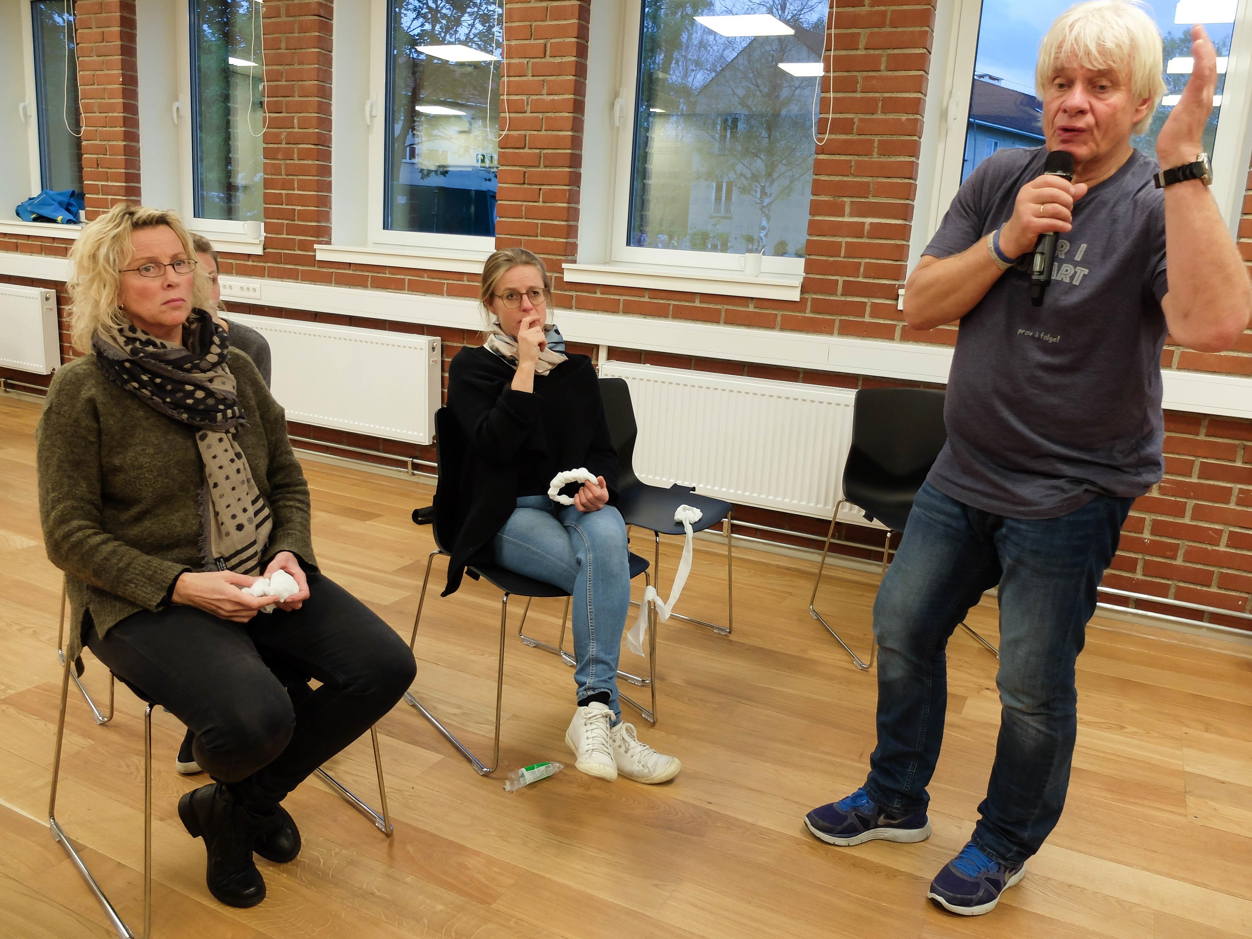 To kvinner sitter og hører på en mann som foreleser om førstehjelp i hverdagen.