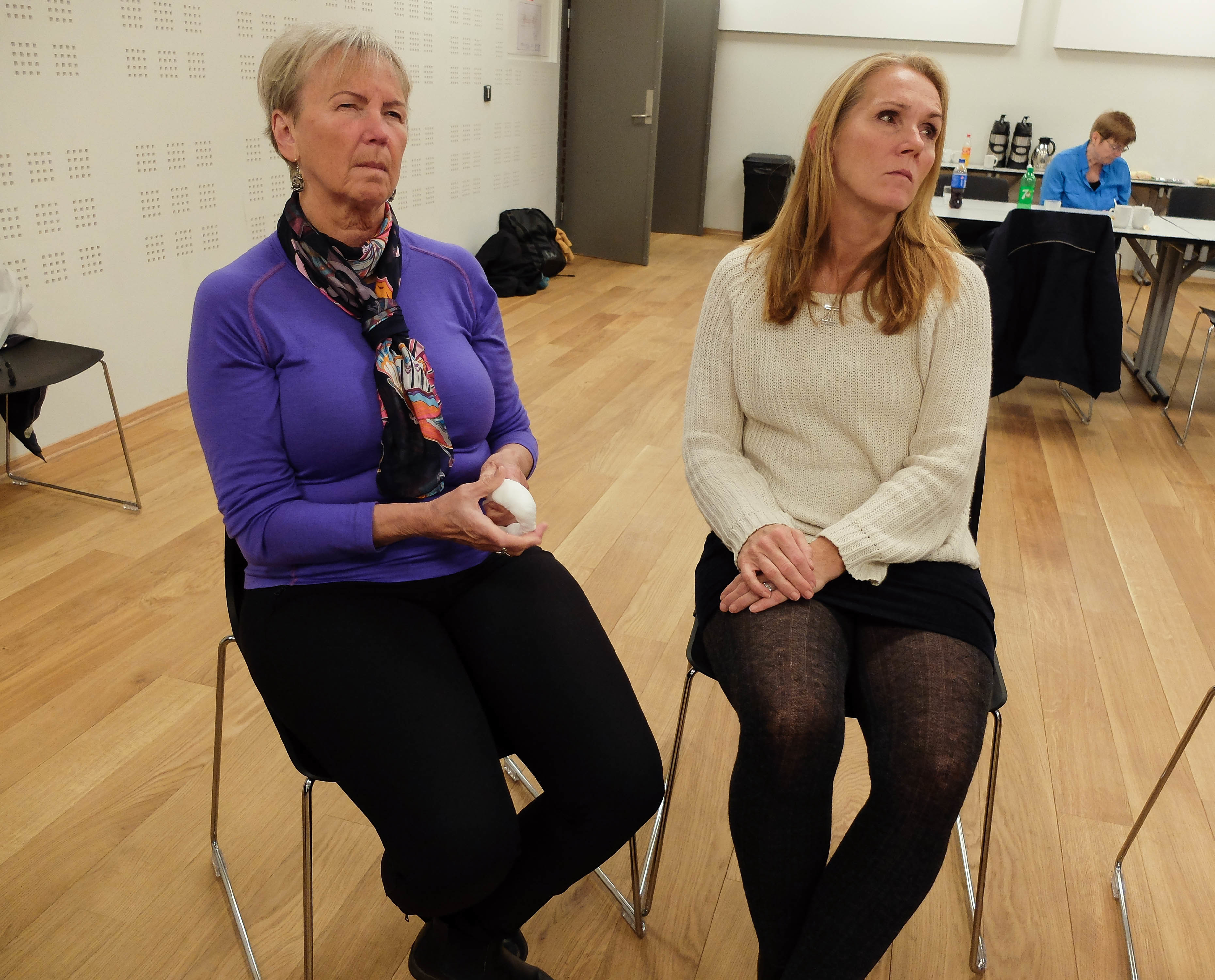 To kvinner sitter og hører forelesning om førstehjelp. Hun til venstre er døvblind og har lagd seg en smultringbandasje på venstre hånd. Hun til høyre er tolk.