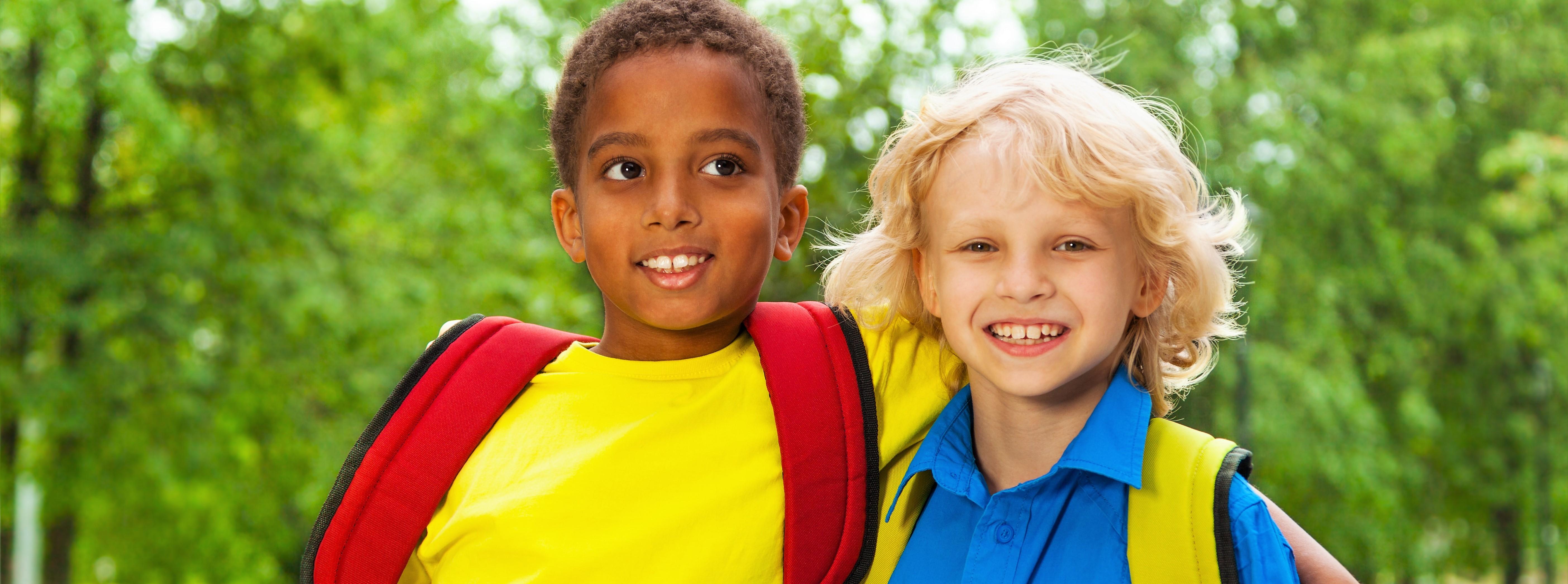 Bilde av to gutter som står skulder ved skulder og smiler