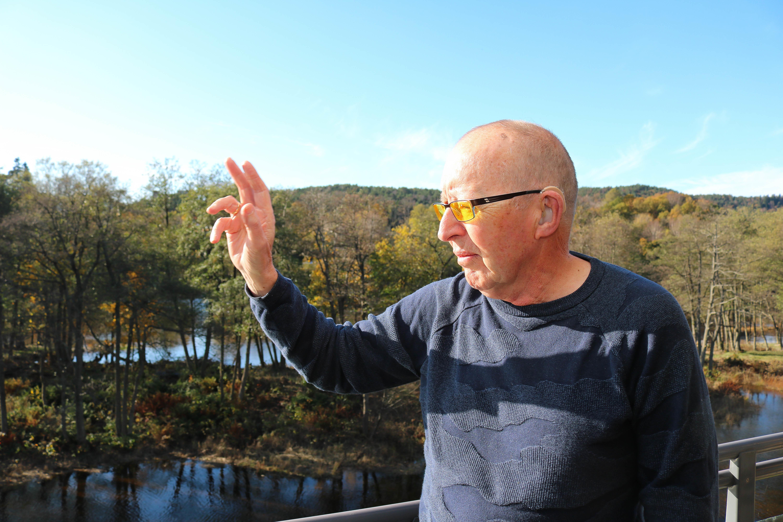 Eldre døvblind mann med gule fargefilterbriller står på sin veranda og bruker sin høyre hånd til å vise retningen til Kristiansand sentrum.