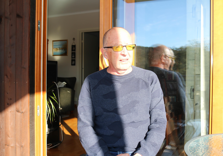 Eldre døvblind mann med gule fargefilterbriller står på sin veranda med sterk ettermiddagssol lysende mot seg.