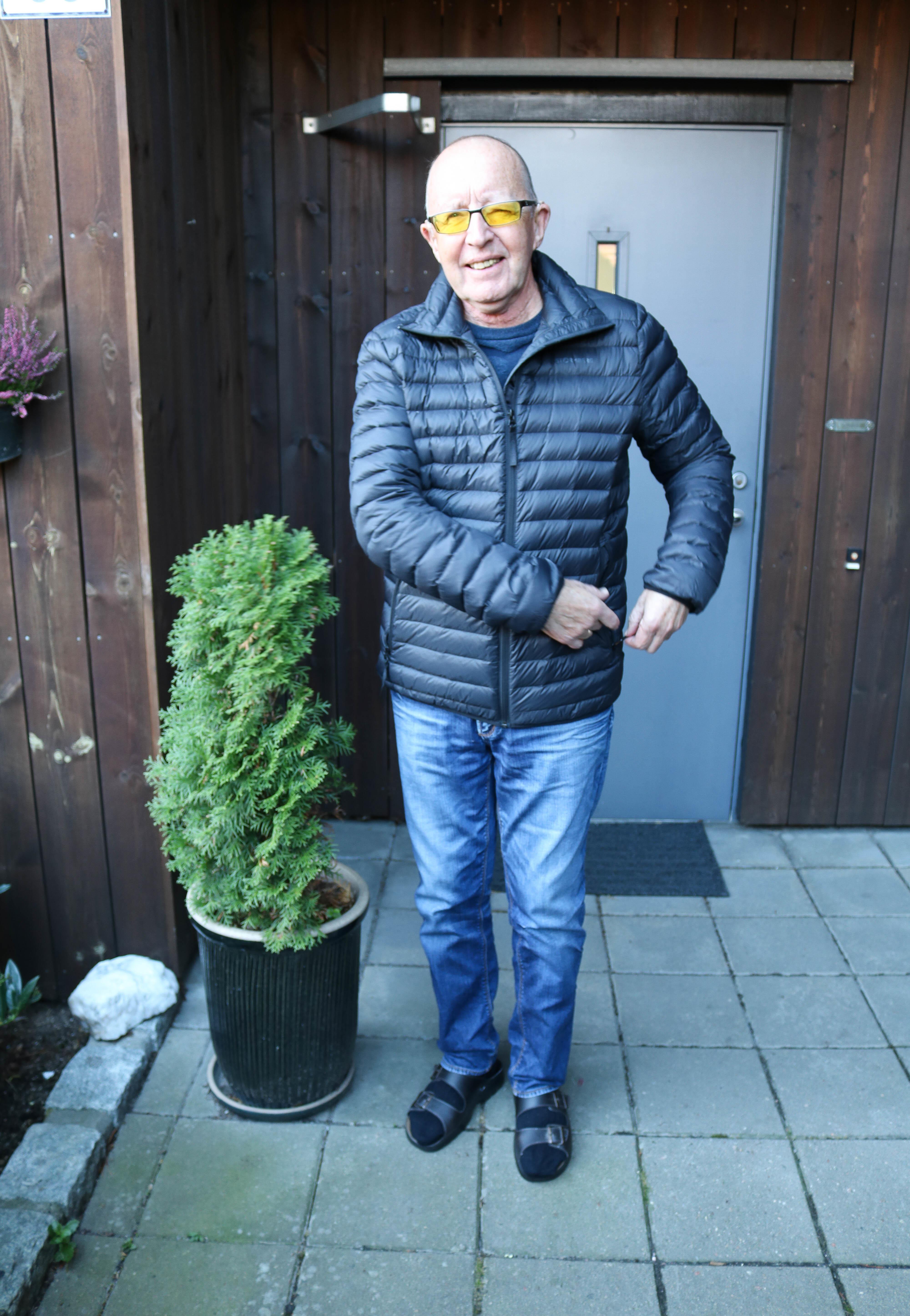 Eldre døvblind mann med gule fargefilterbriller og mørkeblå dunjakke står foran sin egen ytterdør.