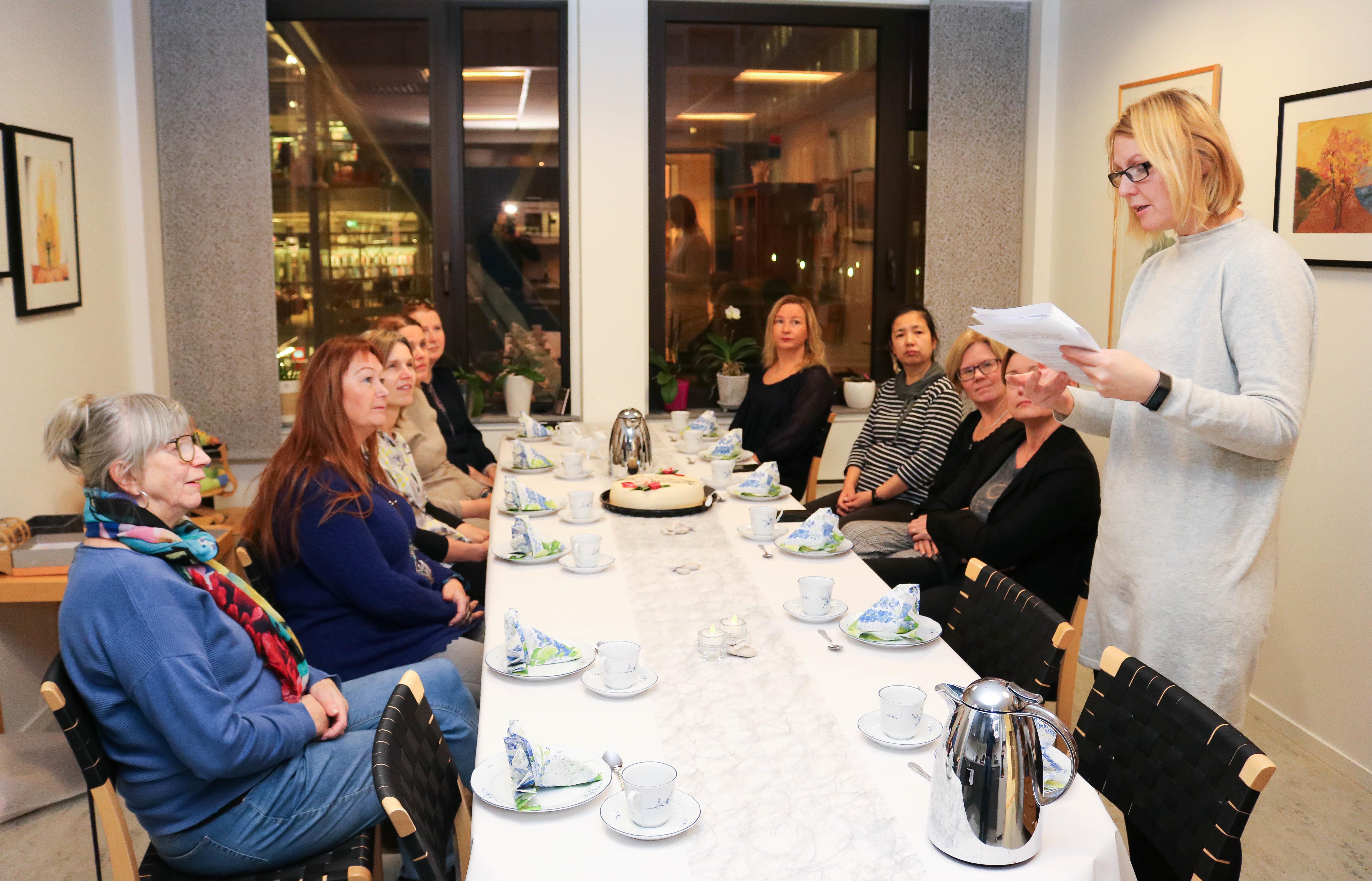 10 kvinner er samlet på et pauserom til kaffe og marsipankake, i anledning lanseringen av en ny prosjektrapport. Deres leder står oppreist til venstre og takker prosjektdeltakerne for vel utført arbeid.