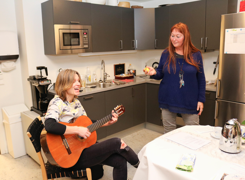 To kvinner spiller og synger sammen. Hun til venstre sitter og spiller på en gitar mens hun synger, mens hun til høyre står og synger.