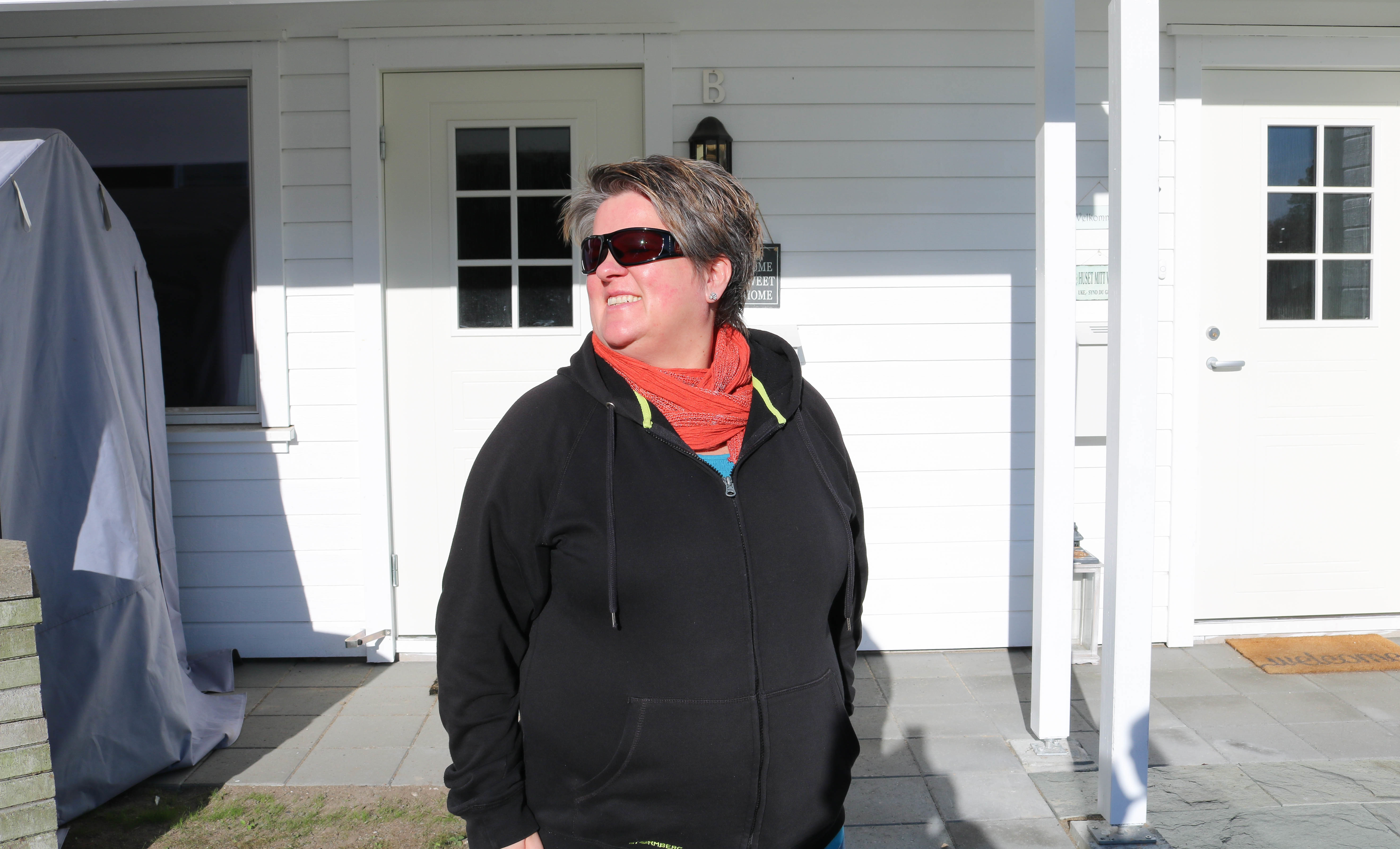 Døvblind kvinne står utenfor sitt hus og smiler. Sola skinner på henne og hun har på seg sorte solbriller. Hun har på seg svart hettegenser og i halsen et rødt sjal.