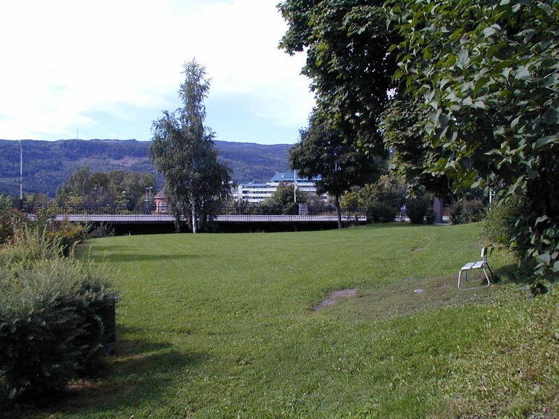 Park, plen med hvit benk, Fåberggata i bakgrunnen