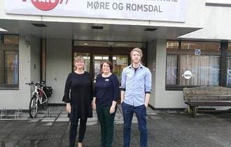 To kvinner og en mann står foran inngang og skiltet til NAV hjelpemiddelsentral Møre og Romsdal i Ålesund.
