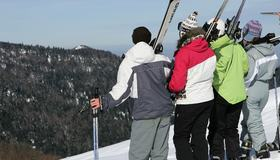 Bilde av ungdom som står med slalomutstyr og ser utover en snødekt bakke i skogen