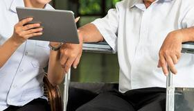 Bilde av pleier og pasient som sitter med nettbrett