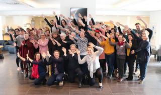 Gruppebilde av nærmere femti smilende rådgivere fra NKDBs ulike enheter. Alle strekker armene sine til høyre, som en bølge eller vifte.