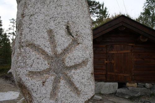 Skulptur i stein foran tømmerkoia