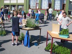 Unger og voksne rundte bordene hvor elevene selger blomster