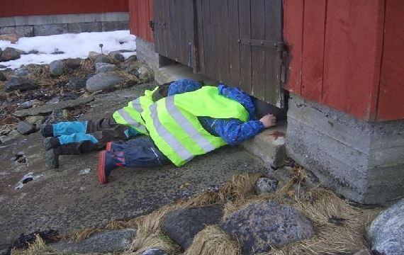 Barn som ligg og ser under døra på eit naust
