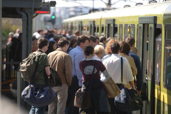 illustrasjon av et pendlertog med mange ventende passasjerer
