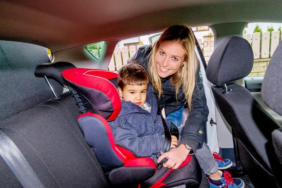 illustrasjon av trafikksikkerhet. Barn spennes fast i sikkerhetsselen i bil