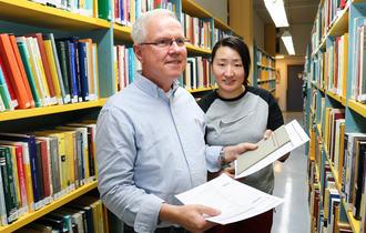 Bibliotekar Edvard Johan Strand sammen med sin funksjonsassistent Lin Jia inne på NH-biblioteket, Universitetsbiblioteket i Tromsø.