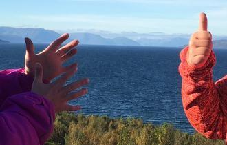 Hender i bevegelser foran landskap med skog, sjø og fjell i Alta-området.