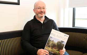 Magnus Tollefsrud sitter i en sofa og viser fram en prosjektrapport.