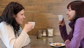 Bilde av to kvinner som drikker kaffe på kafe.