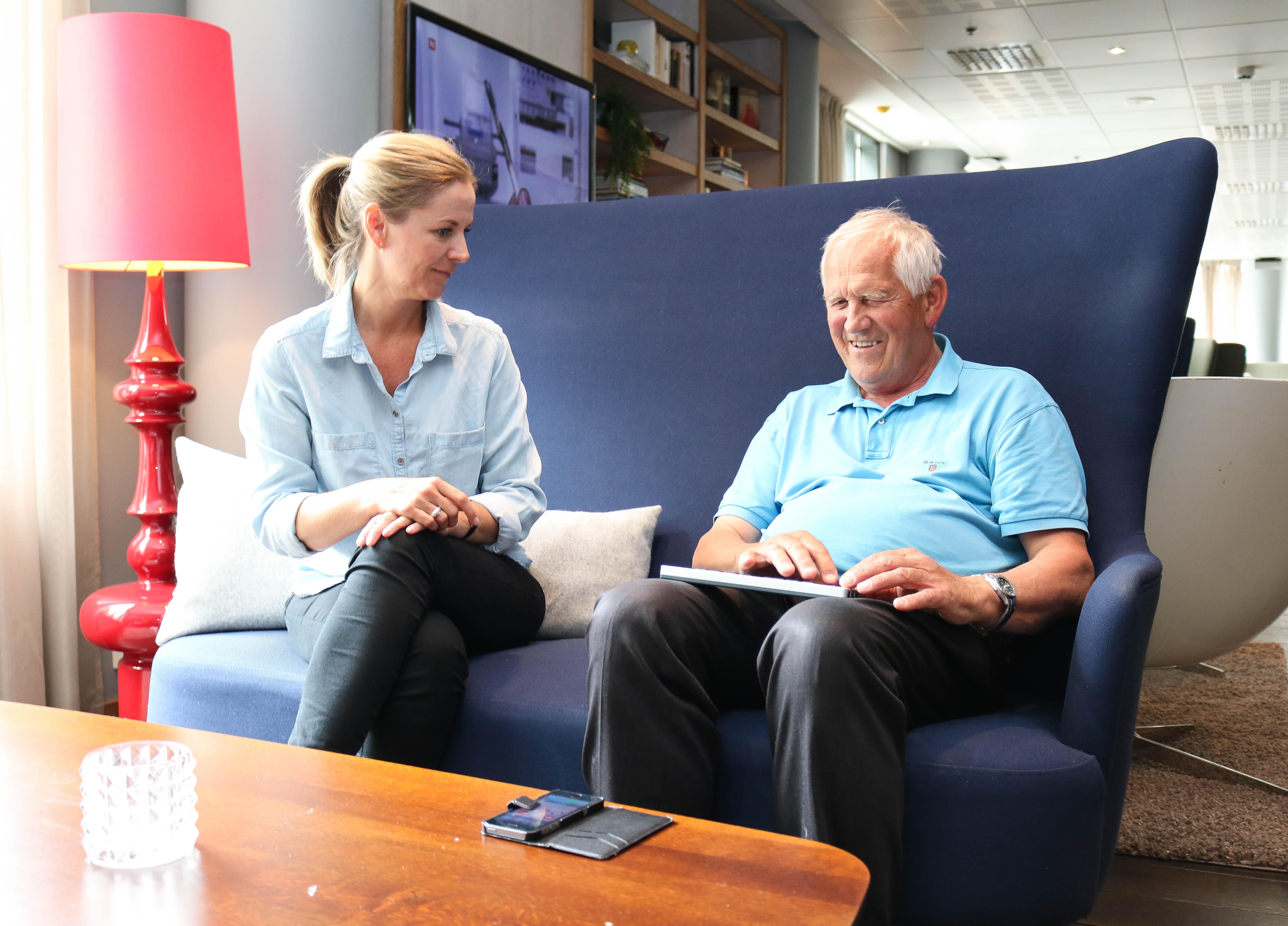 En eldre FNDB-medlem bruker leselist for å lese nyheter på sin mobil, til venstre sitter en kvinnelig tolk-ledsager og følger med.