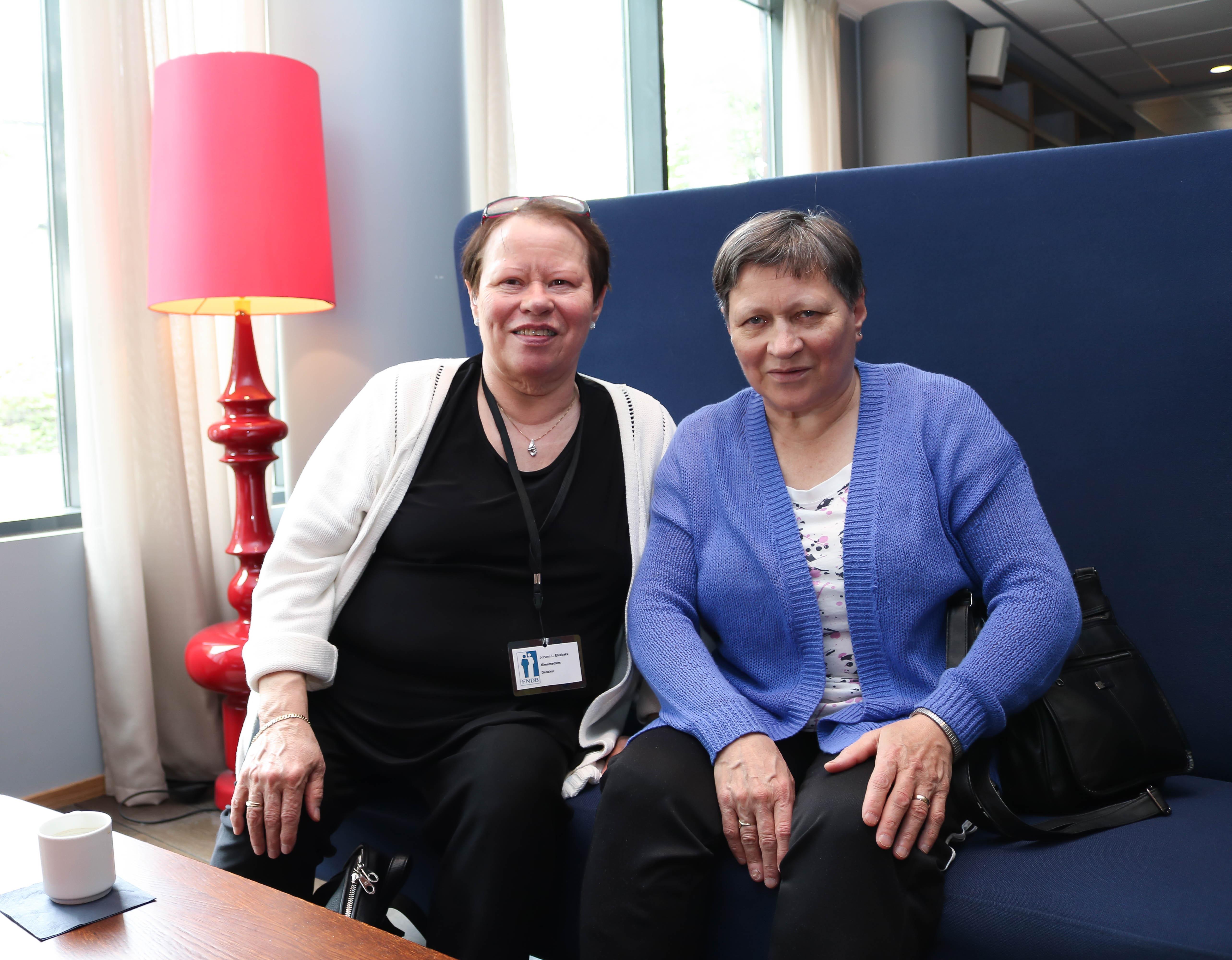 To kvinnelige FNDB-medlemmer sitter sammen i en mørkeblå sofa.