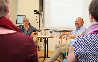 Randi Sørlie intervjuer Bertil Bjerkan, sett mellom skuldrene til to sittende kvinner.