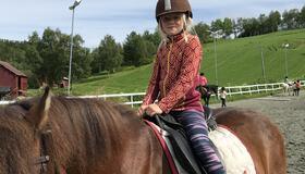 Jente rir på hest