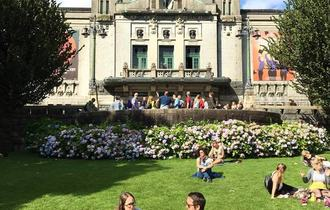 Den Nationale Scene i Bergen en solfylt lørdag, flere grupper med unge folk sitter i gresset foran teateret.