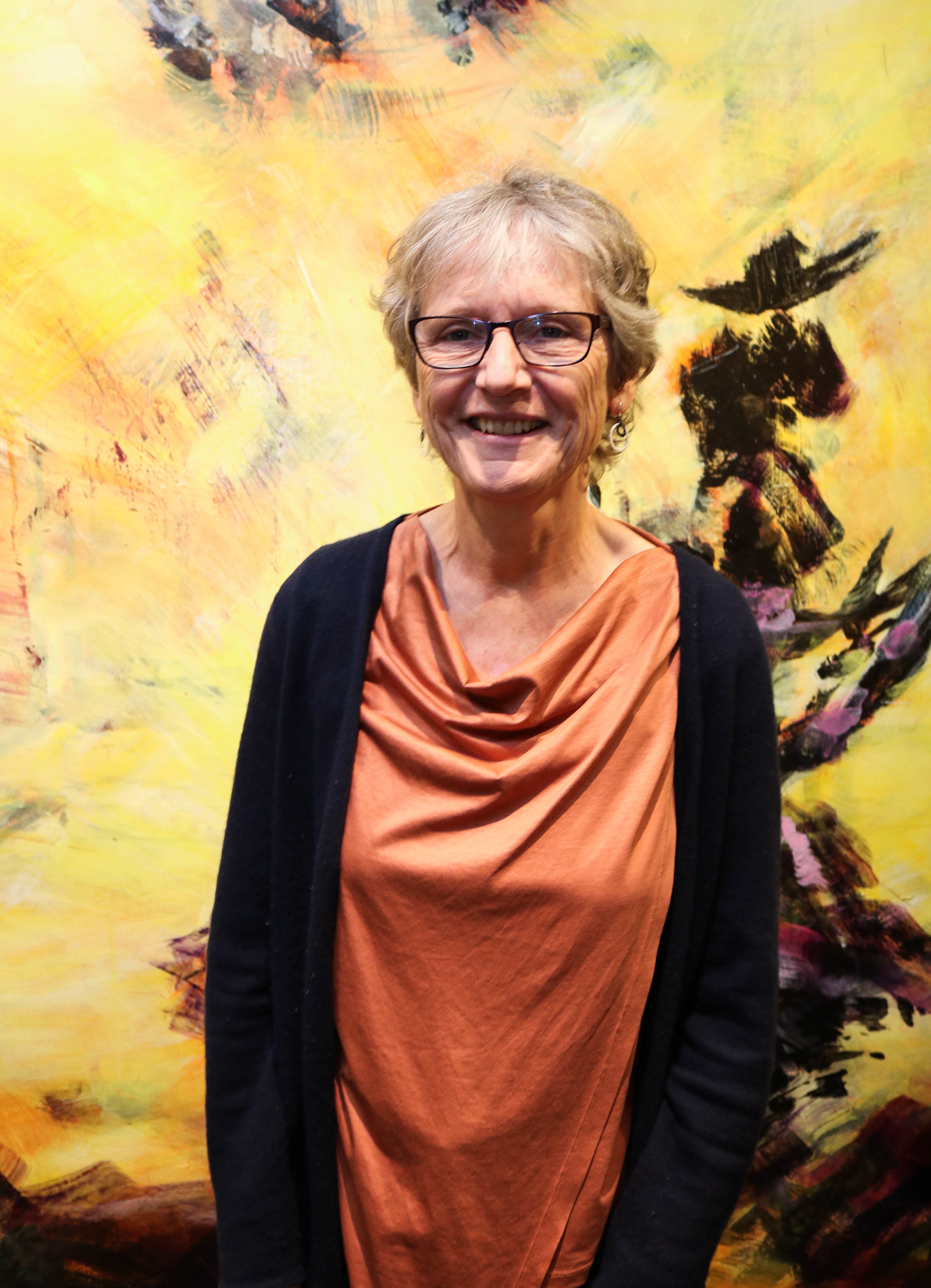 Marianne Disch, portrettfoto foran et gulspraglete maleri. Høydebilde.
