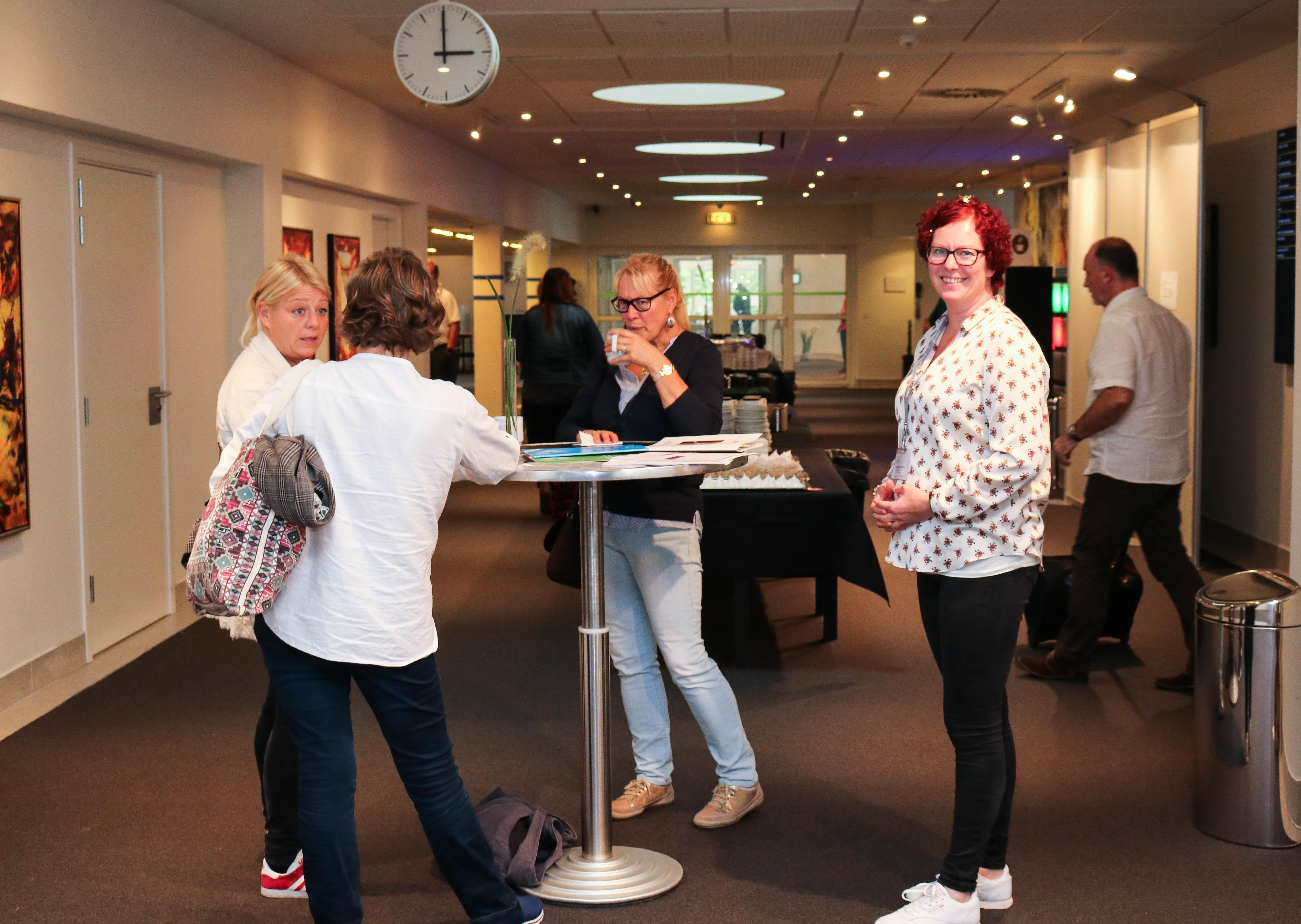 Fire kvinnelige konferansedeltakere ved et rundt bord, i en av pausene mellom rekken med workshops.