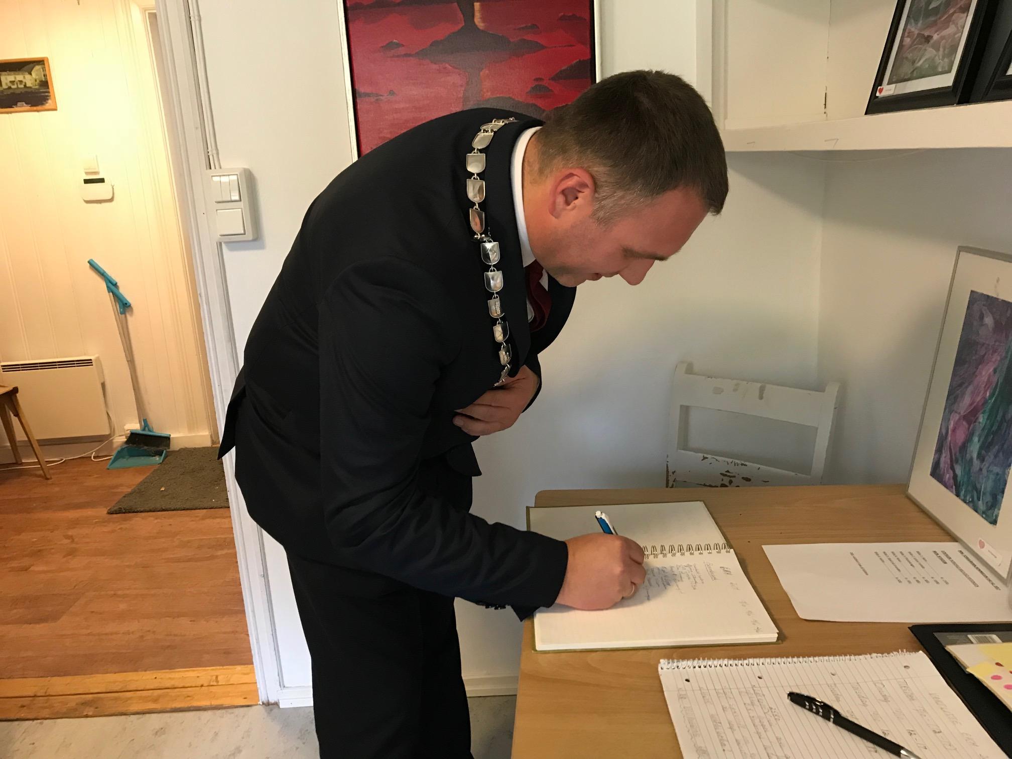 Bilde av varaordfører Ole Herman Sveian som signerer besøksprotokollen